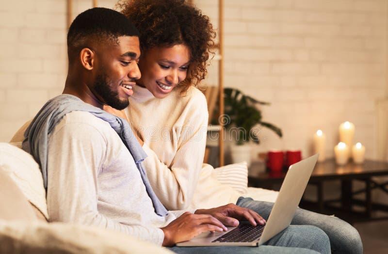 Jovens casados usando laptop à noite confortável de inverno fotografia de stock