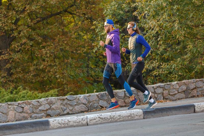 Jovens casais correndo no parque de outono pela manhã foto de stock royalty free