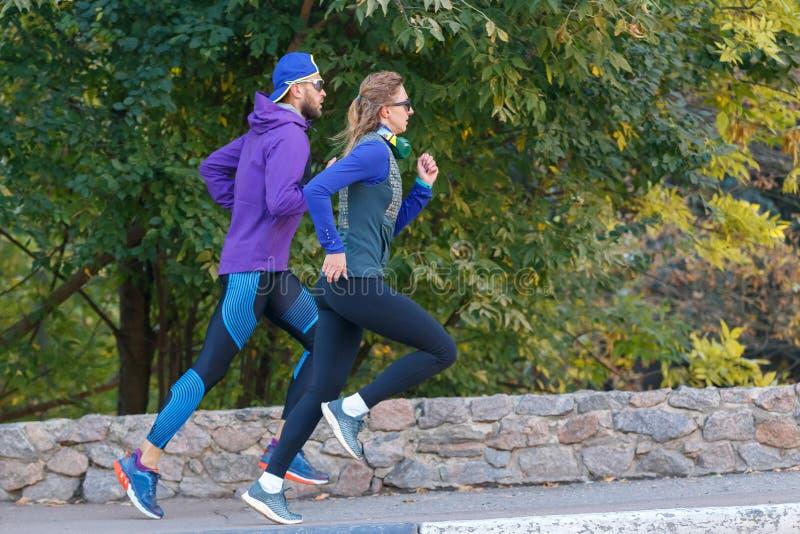 Jovens casais correndo no parque de outono pela manhã foto de stock