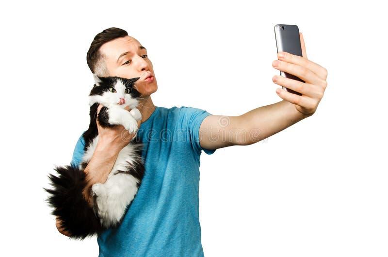 Jovens caucasianos engraçados em t-shirt azul com tiros de gato na câmara do telefone inteligente selfie sobre fundo cinza-claro foto de stock royalty free