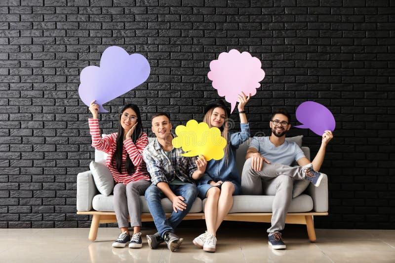 Jovens com as bolhas vazias do discurso que sentam-se no sofá perto da parede escura foto de stock