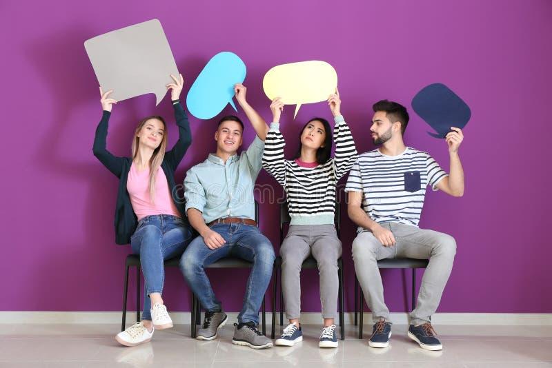 Jovens com as bolhas vazias do discurso que sentam-se perto da parede da cor fotos de stock