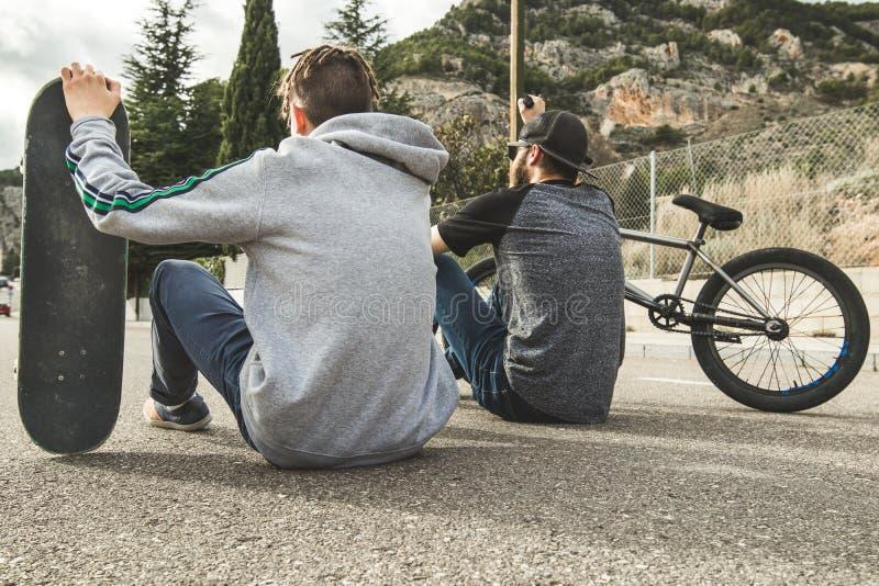 Jovens com bicicletas e skates na cidade Esportes urbanos e extremos para jovens fotografia de stock royalty free