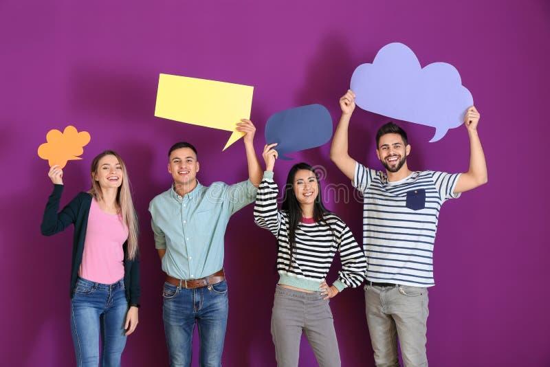 Jovens com bolhas vazias do discurso no fundo da cor fotos de stock royalty free