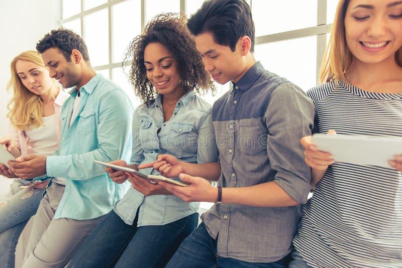 Jovens com dispositivos fotos de stock