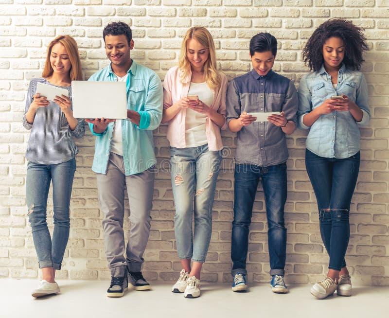 Jovens com dispositivos imagem de stock royalty free