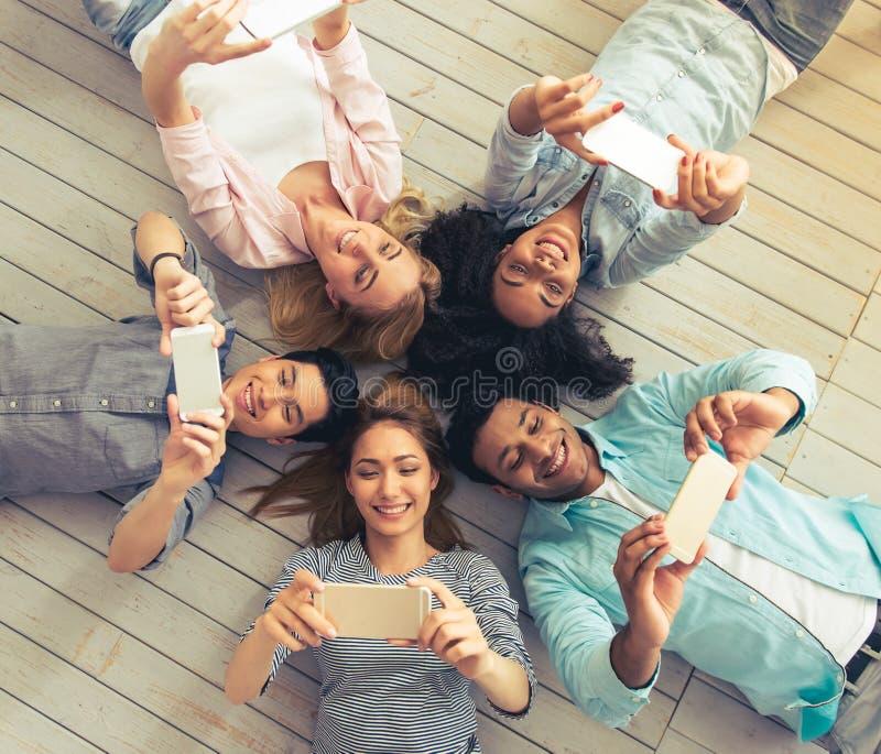 Jovens com dispositivos fotografia de stock royalty free
