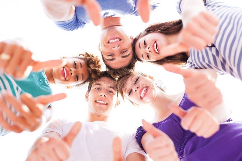 Jovens com polegares acima foto de stock