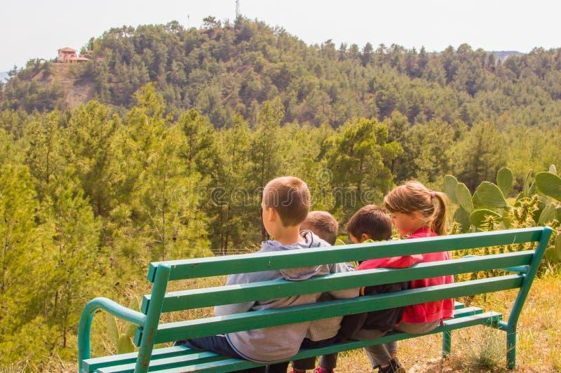 Jovens crianças que sentam-se no banco foto de stock royalty free