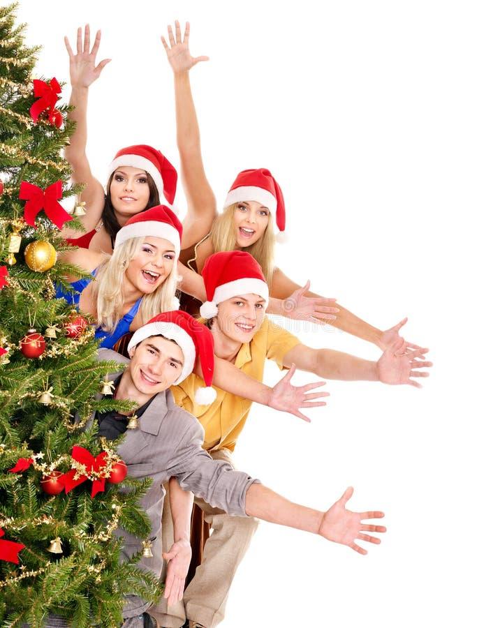 Jovens do grupo pela árvore de Natal. fotografia de stock