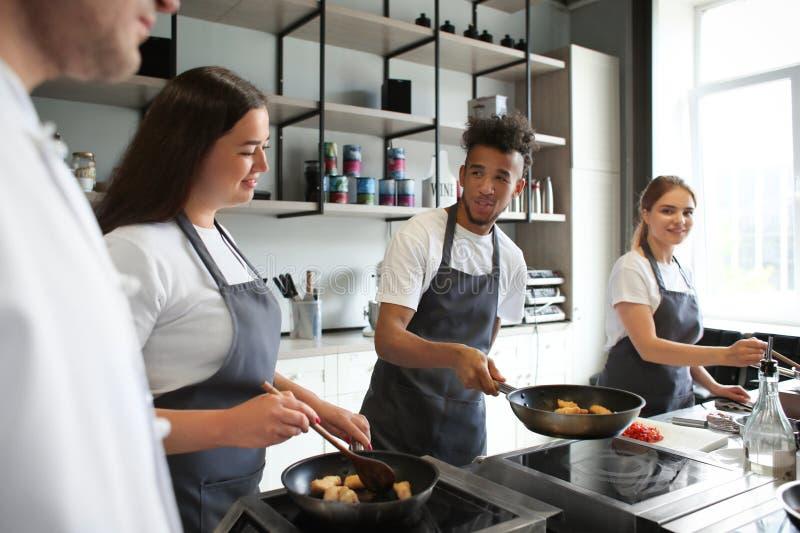Jovens durante aulas de culinária na cozinha do restaurante imagem de stock royalty free