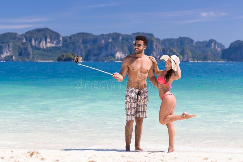 Jovens em férias de verão da praia, par que toma a beira-mar da foto de Selfie a água azul fotografia de stock