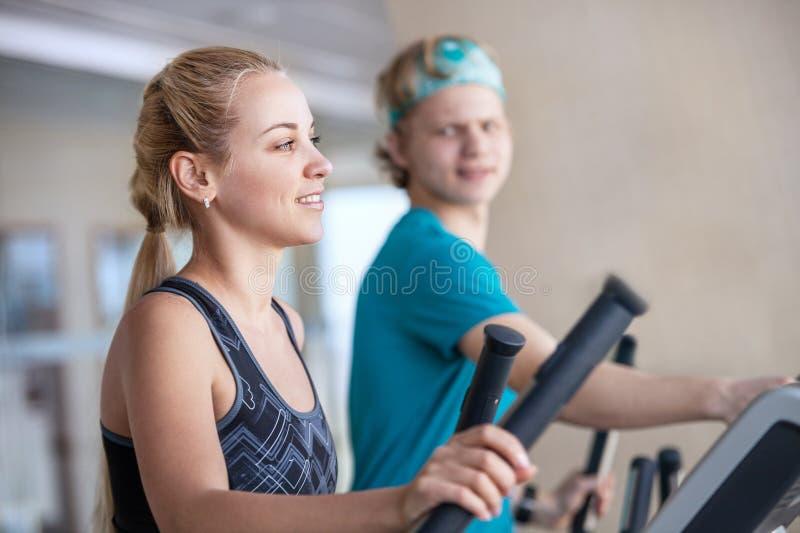 Jovens em simuladores corridos no gym fotos de stock royalty free