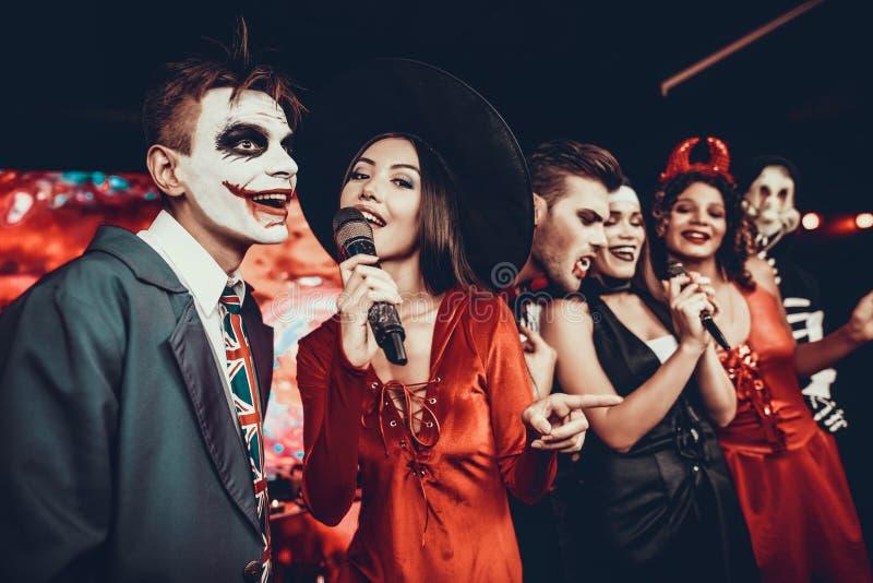 Jovens em trajes de Dia das Bruxas que cantam o karaoke foto de stock