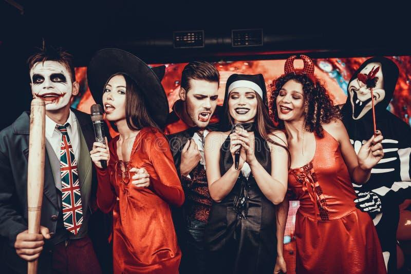 Jovens em trajes de Dia das Bruxas que cantam o karaoke imagens de stock