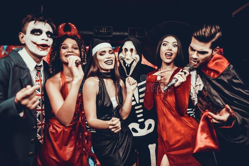 Jovens em trajes de Dia das Bruxas que cantam o karaoke fotos de stock royalty free