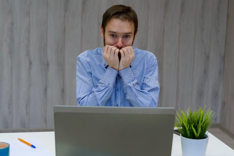 Jovens empresários vestidos de camisa azul enquanto usam laptop no escritório em antecipação a algo agradável fotografia de stock