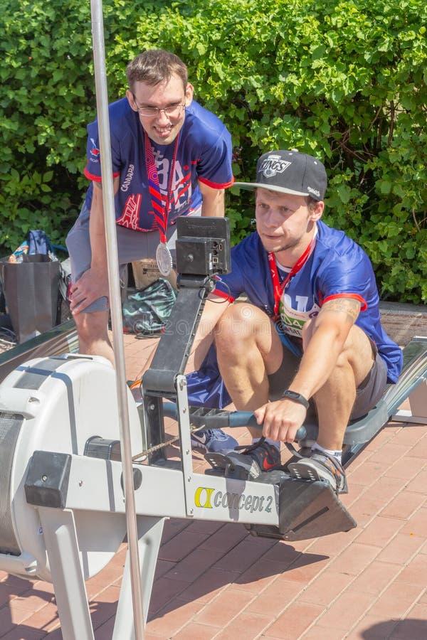 Jovens esportivos estão treinando em simuladores no Embankment do Rio Volga foto de stock
