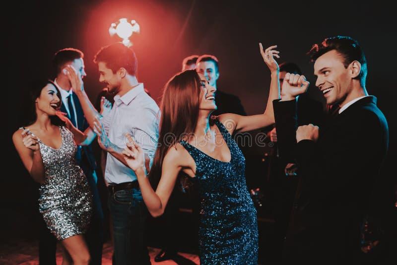 Jovens felizes que dançam no partido do ano novo imagens de stock royalty free