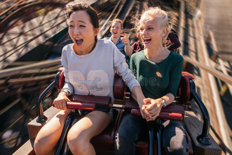 Jovens felizes que montam uma montanha russa foto de stock royalty free