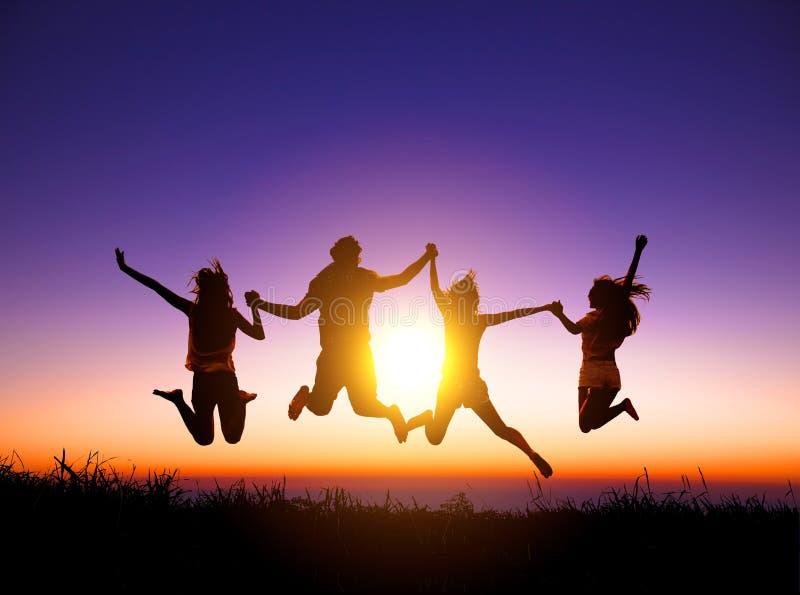 jovens felizes que saltam na montanha imagens de stock