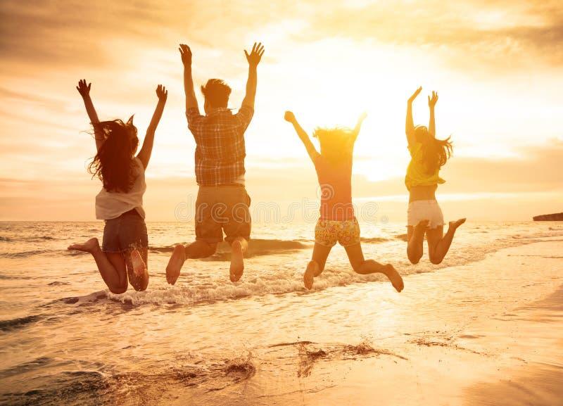 jovens felizes que saltam na praia fotos de stock