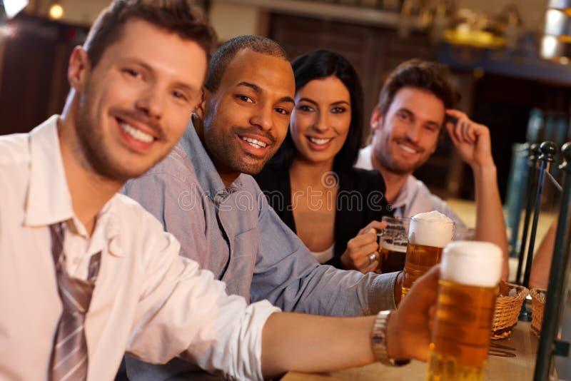 Jovens felizes que sentam-se no bar, cerveja bebendo fotos de stock