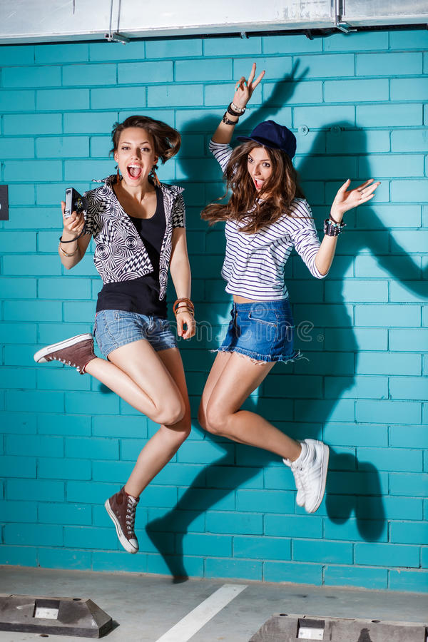 Jovens felizes que têm o divertimento e que saltam na frente do tijolo azul foto de stock royalty free