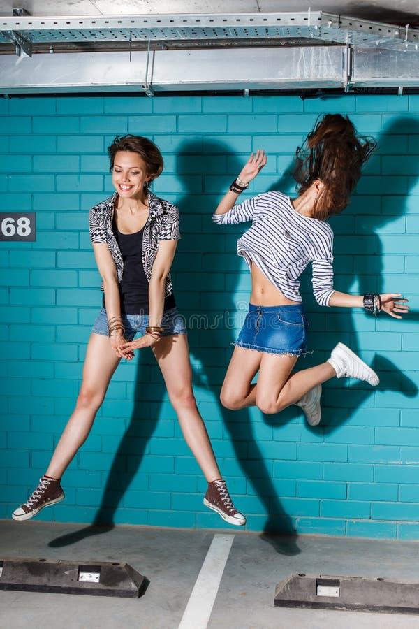 Jovens felizes que têm o divertimento e que saltam na frente do tijolo azul imagens de stock royalty free