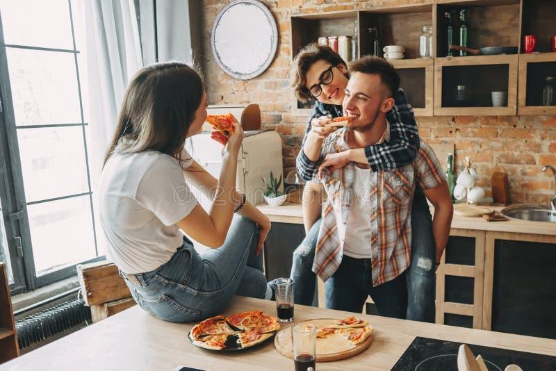 Jovens felizes que têm o divertimento junto, sorrindo, comendo a pizza fotos de stock
