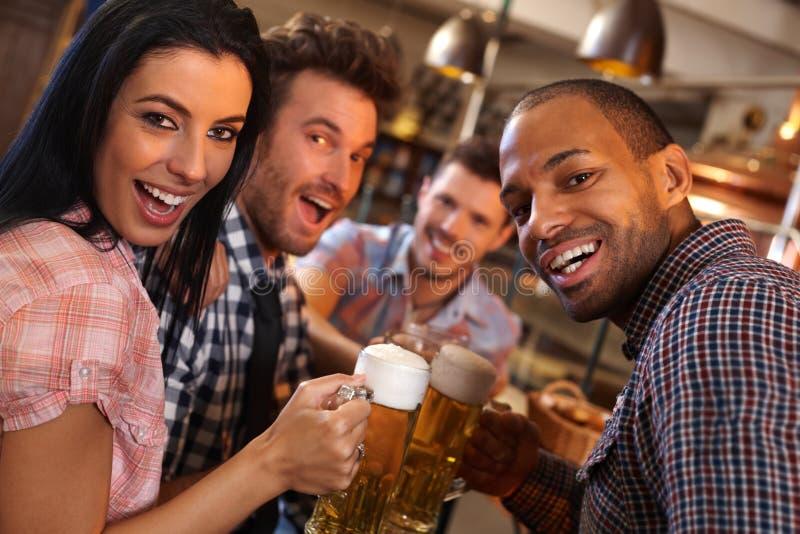Jovens felizes que têm o divertimento na barra fotografia de stock