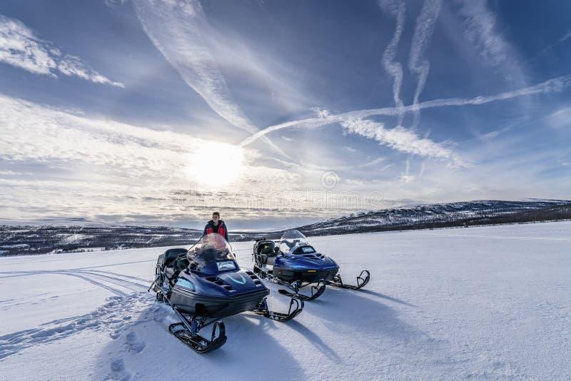 Jovens ficam atrás de dois snomobiles azuis nas montanhas de neve de inverno, neve virgem fria, sol brilhante com halo ao redor,  foto de stock