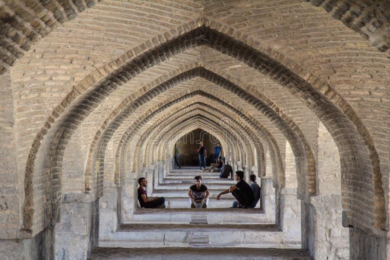 Jovens iranianos que recolhem sob a ponte de Kahju, uma das pontes principais do coty, discutindo e socializando fotografia de stock royalty free