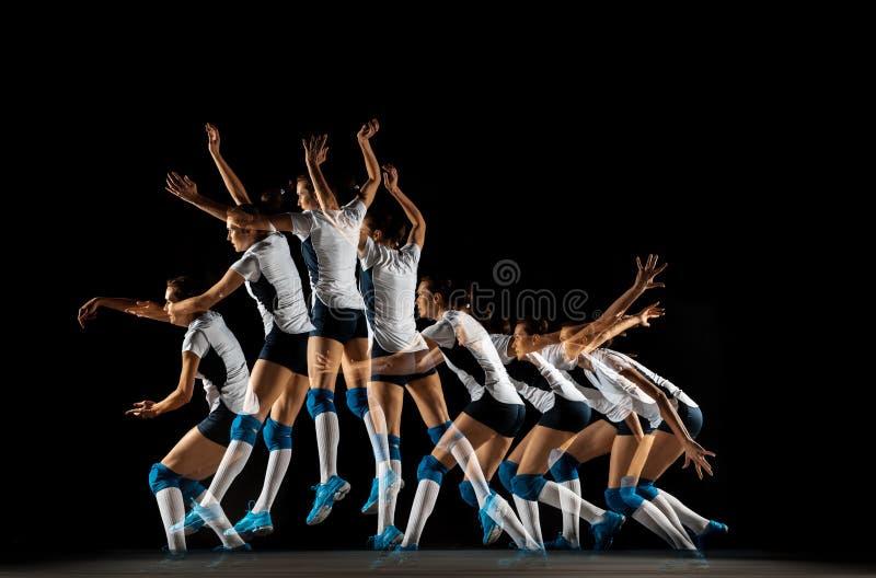 Jovens jogadoras de vôlei isoladas em fundo de estúdio negro fotografia de stock