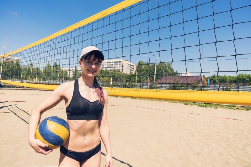 Jovens jogando voleibol de praia Campeonato de voleibol de praia Jogos de esporte ao ar livre mulher fica de pé com um voleibol fotos de stock royalty free