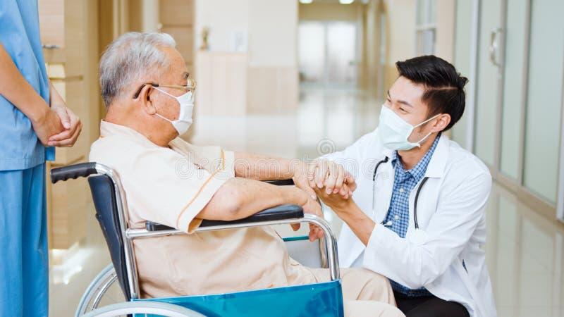 Jovens médicos asiáticos se agarram de mãos dadas e falam com o paciente adulto sênior em cadeira de rodas no corredor do hospita imagens de stock