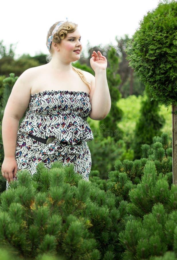 Jovens mais a menina do tamanho entre as plantas sempre-verdes no jardim fotografia de stock royalty free