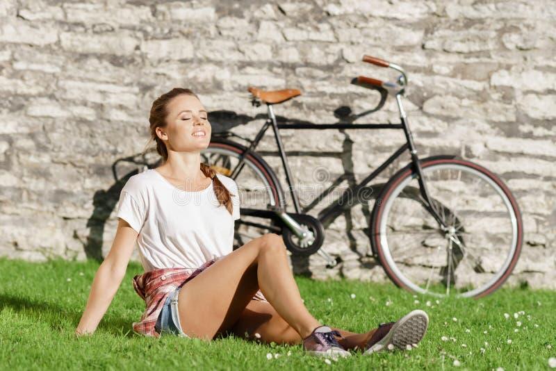 Jovens, menina atrativa bonita do moderno que relaxa no parque foto de stock royalty free