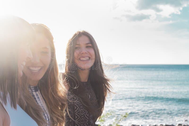 3 jovens mulheres andam na praia que olha se, rindo e passando o tempo livre junto Em um dia de ver?o agrad?vel Com sol foto de stock