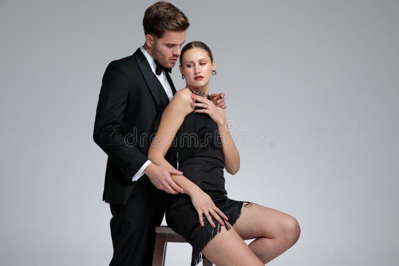 Jovens mulheres assentadas bonitas que estão sendo abraçadas por seu noivo considerável foto de stock royalty free