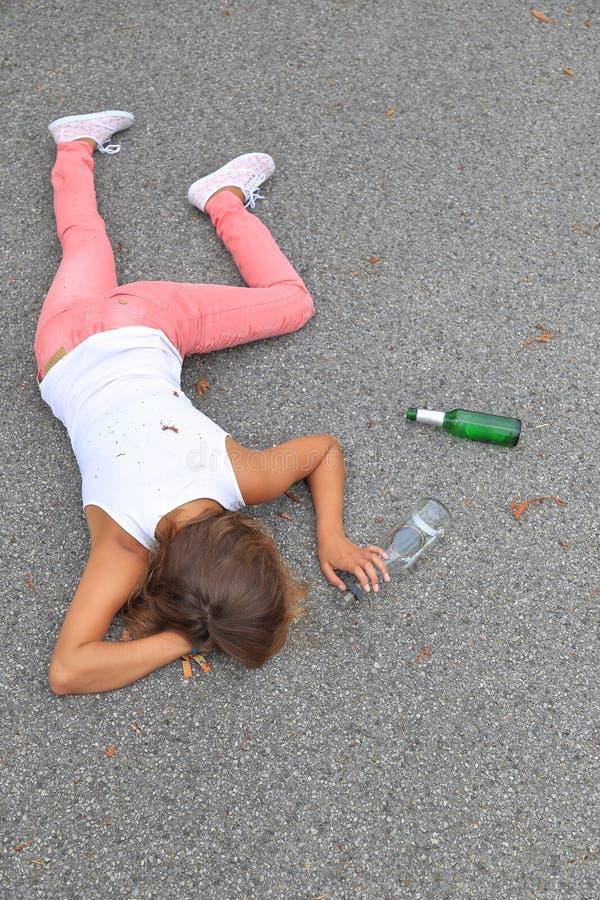 Jovens mulheres bêbados que encontram-se na rua imagem de stock royalty free