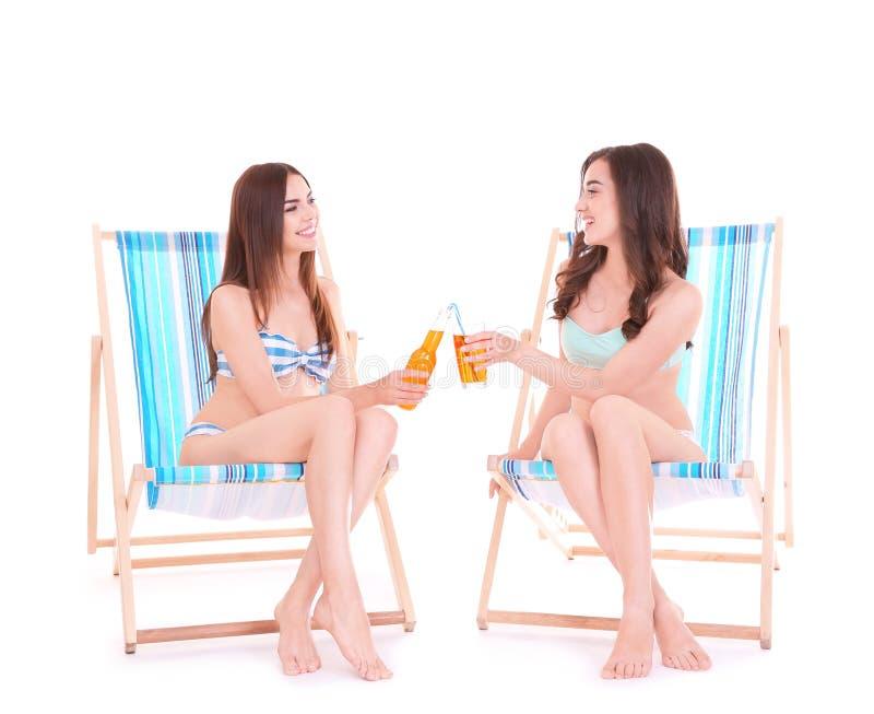 Jovens mulheres bonitas com assento das bebidas alcoólicas foto de stock