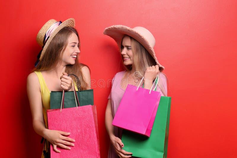 Jovens mulheres bonitas com os sacos de compras no fundo da cor imagem de stock royalty free