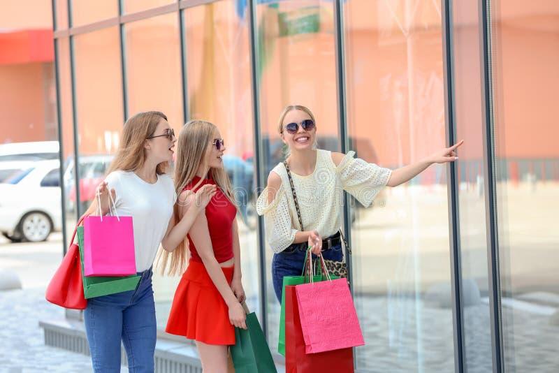 Jovens mulheres bonitas com os sacos de compras que olham a mostra da loja fotos de stock royalty free