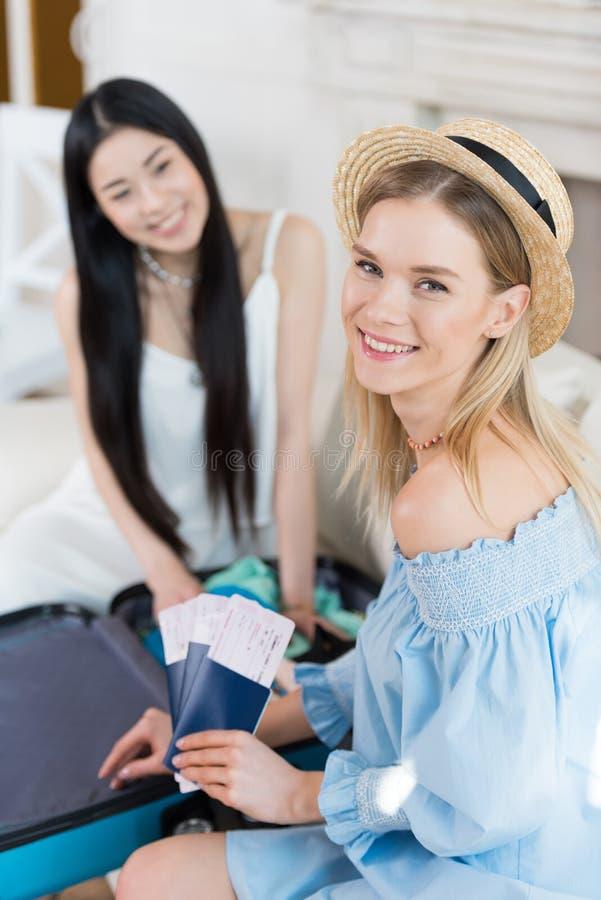 Jovens mulheres bonitas com passaportes e bilhetes que embalam a mala de viagem imagem de stock royalty free