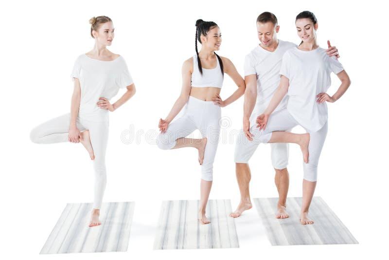 Jovens mulheres bonitas de sorriso que praticam a ioga com instrutor fotografia de stock royalty free