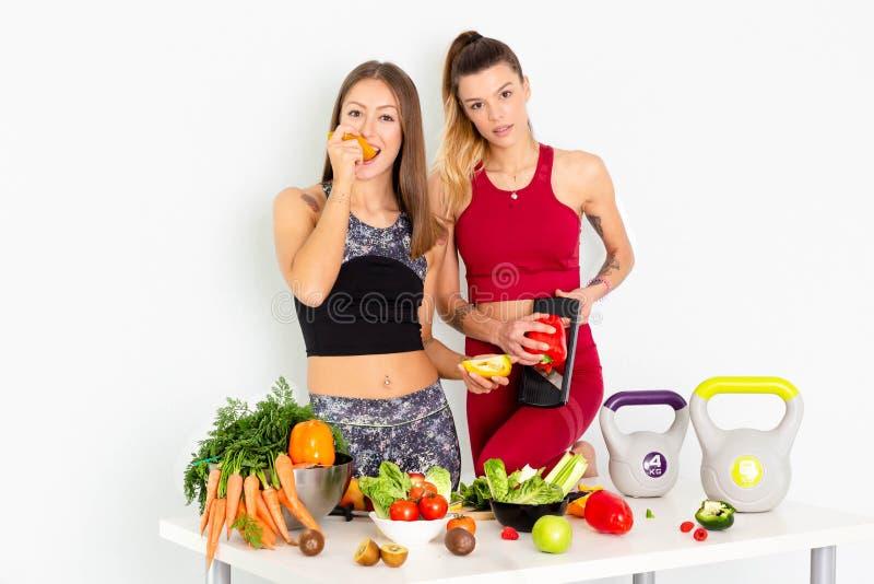 Jovens mulheres bonitas que comem frutas e legumes saudáveis no fundo branco Faça dieta o conceito - Imagem foto de stock