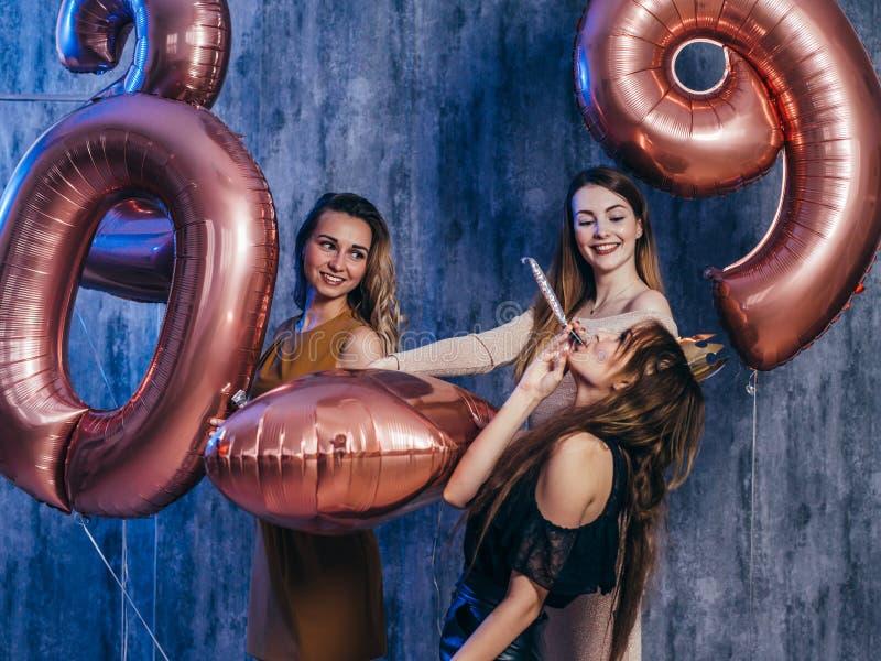 Jovens mulheres bonitas que comemoram o jogo guardando balões Ano novo, Natal, xmas fotografia de stock royalty free