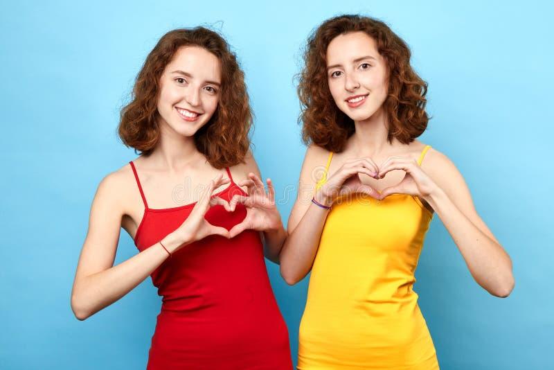 Jovens mulheres bonitas que mostram a símbolos do coração o conceito romântico foto de stock royalty free