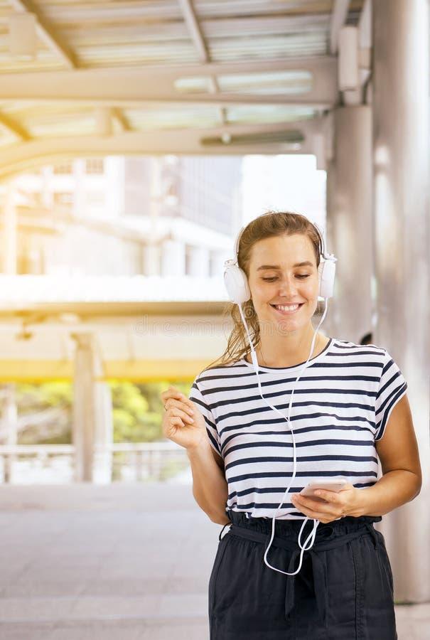 Jovens mulheres caucasianos bonitas que usam o fones de ouvido e escutando com dança a música exterior, boa atitude, pensamento p foto de stock